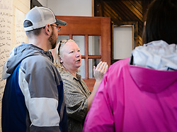 Joanne Waterman (second from left) answers visitor's questions during a recent open house celebrating the completion of the restoration of the fire hall on the grounds of historic Fort William H. Seward in Haines, Alaska.<br /> <br /> The fire hall was restored over a two-year period by owners Waterman and Phyllis Sage who also own the fort&rsquo;s original guardhouse, now a bed and breakfast, located next door to the fire hall.<br /> <br /> After being absent from the historic Fort Seward skyline since approximately the 1930s, the 60-foot tower of the fort&rsquo;s fire hall has been restored to its original height. The building and tower, built around 1904 in Haines, Alaska, was shortened to approximately half its height in the 1930s for unknown reasons. The restoration included rebuilding a missing 35-foot section of the 60-foot tower whose purpose was to dry fire hoses. The tower restoration was completed by building its four sections on the ground and then hoisting those sections with a crane into place on top of each other.<br /> <br /> Through the years, the historic Fort Seward area, a former U.S. Army post, has been referred to as Fort William H. Seward, Chilkoot Barracks, and Port Chilkoot. The National Historic Landmarks listing record for the fort says that &quot;Fort Seward was the last of 11 military posts established in Alaska during the territory's gold rushes between 1897 and 1904. Founded for the purpose of preserving law and order among the gold seekers, the fort also provided a U.S. military presence in Alaska during boundary disputes with Canada. The only active military post in Alaska between 1925 and 1940, the fort was closed at the end of World War II.&rdquo; <br /> <br /> The bottom portion of the fire hall is being leased as commercial space. Due to fire code restrictions there is no public access to the upper portion of the tower.