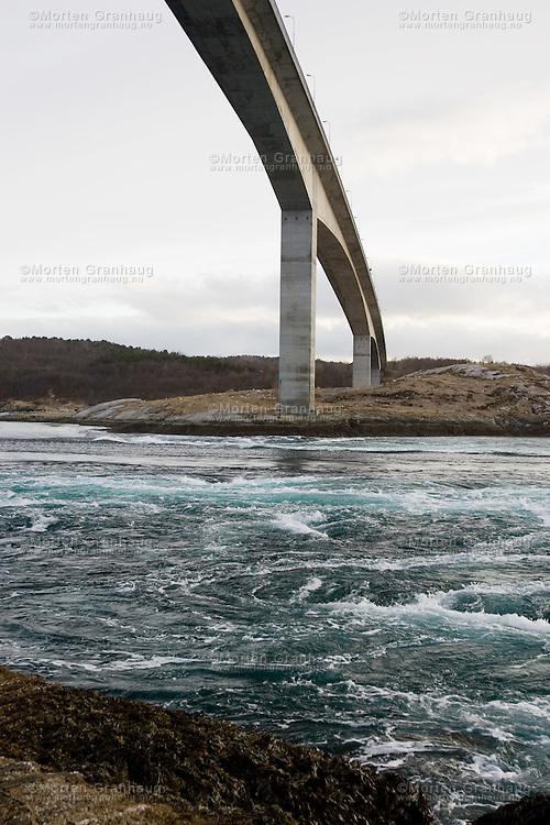 Saltstraumen is a sound with a strong tidal current located in Nordland 30 km east of the city of Bodø, Norway. The narrow channel connects the outer Saltfjord with its extension, the large Skjerstadfjord. It is the strongest tidal current in the world. Up to 400 million m³ (tonnes) of seawater forces its way through a 3 km long and 150 m wide strait every six hours, with water speeds reaching 20 knots (about 37 km/h). Vortices up to 10 m in diameter and 5 m in depth are formed when the current is at its strongest; this feature is commonly known as a whirlpool or maelstrom...Saltstraumen er verdens sterkeste tidevannsstrøm og ligger mellom Knaplundøya og Straumøya i Bodø kommune i Nordland. Den forbinder Ytre Saltenfjord med Skjerstadfjorden (Indre Saltenfjord). Strømmen blir til når tidevannet fyller denne. Strømmen er 3 km lang og på det smaleste bare 150 m bred, hastigheten på strømmen er omtrent 22 knop (40 km/t). Fartøyer kan passere Saltstraumen i ca. 2 timer etter hver flo og fjære. Under nippflo passerer større vannmasser gjennom Saltstraumen enn gjennom Norges største elver i flomtida: i løpet av cirka 6 timer presses 372 millioner kubikkmeter sjøvann gjennom en 150 meter bred og 31 meter dyp passasje...Høydeforskjellen på havflaten mellom innersiden og yttersiden av det trange sundet kan være så mye som 3 fot (1 meter). I et forsøk på å jevne ut de to sidene, øker vannet sin hastighet og minner mest om et elvestryk, som renner begge veier.