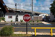 A red and white Stop Sign by a parking lot next to a yellow exit barricade with a bridge and train trestle in the background