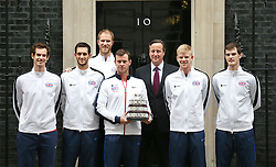 © Licensed to London News Pictures. 01/12/2015. London, UK.  Britain's winning Davis Cup team (L-R) Andy Murray, James Ward, Dom Inglot, Captain Leon Smith, Kyle Edmund and Jamie Murray stand on the steps of 10 Downing Street with Prime Minister David Cameron (3L). Photo credit: Peter Macdiarmid/LNP