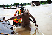 A man is uses fallen electrical power cables and the assistance of a Rescue 1122 worker to help himself across a section of road that has been washed away by flood water...Residents of outlying villages in the district of Muzzafargarh continue to evacuate villages as flood waters continue to cause havoc in South Punjab...