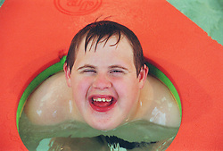 Teenage boy with Downs Syndrome playing with coloured float in public swimming pool,
