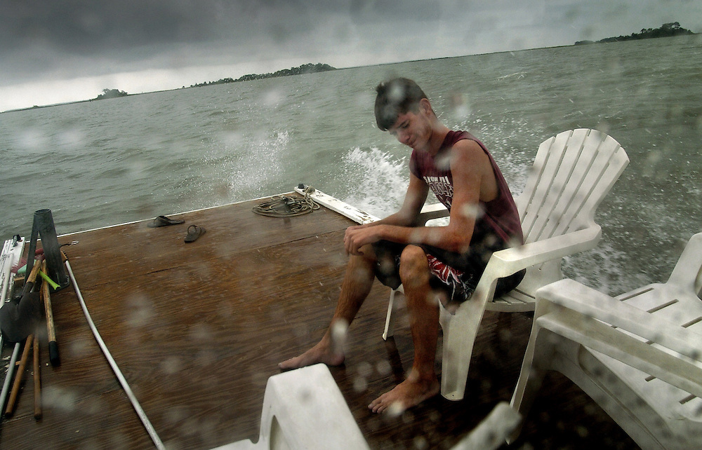 SNOW HILL, MD--8/30/06--Progressing toward remote Islands on a small pontoon boat, Ryan Wooten, 16, turns his head to avoid the spray of choppy waters on a drizzly day while checking clam leases on the Chincoteague Bay near Snow Hill, Md, with Steve Gordon (not pictured).  GLENN FAWCETT