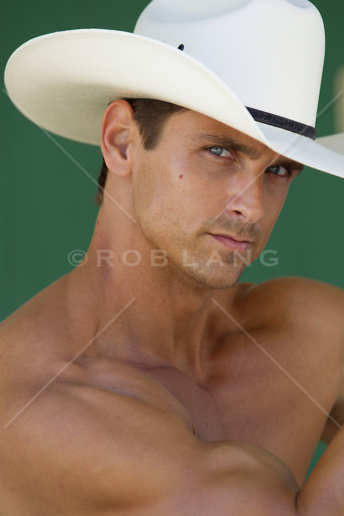 muscular shirtless cowboy against a wall