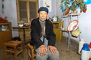 Elderly Chinese man farmer sitting in farmhouse kitchen in village of Poli near Penglai, Shandong Province, China.