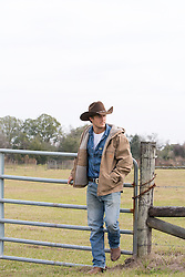 lone cowboy leaning on a fence