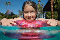 Girl with inflatable raft in swimming pool