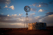 Sunset on a windmill and water tank covered in graffiti on a Mesa near Chinle, Arizona on the Navajo Reservation