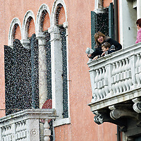 VENICE, ITALY - FEBRUARY 20: A woman and child throw confetti from a balcony  along the Cannaregio Canal during the Venetian Feast on February 20, 2011 in Venice, Italy. During the Venetian Feast a traditional water parade sails from San Marco along the Canal Grande to the  district of Cannaregio where there the crowd waits for the Svolo della Pantegana (flight of the mouse).