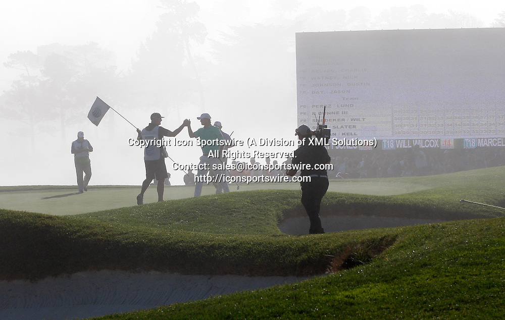 """Feb 15 2015: As the fog creeps in, Brandt Snedeker """"high fives"""" his caddie after winning the AT&T Pebble Beach National Pro-Am in Pebble Beach, CA."""
