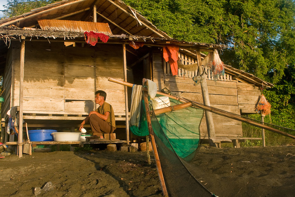 A local tends to his stock of fish fry on a beach in Central Sulawesi