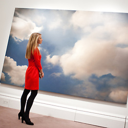 A Sotheby's employee poses in front of a painting 1976 entitled 'Wolke (Cloud)' by Gerhard Richter (Est. £7-9 million) during the press preview of the forthcoming Sotheby's February sales of Impressionist & Modern Art and Contemporary Art in London, including works by Picasso, Bacon, Monet, Richter, Miró, Basquiat.