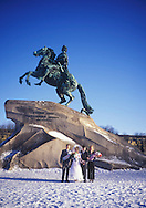 Bride & groom posing  after their wedding in<br /> front of the Bronze Horseman statue in the snow<br /> St. Petersburg, Russia