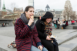 © Licensed to London News Pictures. 22/12/2015. London, UK. A tourist enjoying an ice cream outside, near the Tower of London ice rink today. The Tower of London ice rink has been forced to close today due to safety concerns over high wind speeds.  The UK is experiencing unseasonably mild weather and high winds today. Photo credit : Vickie Flores/LNP