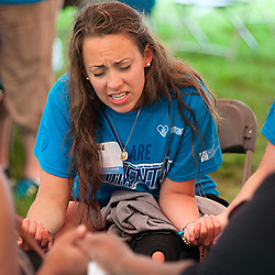 25 JULY 2015 -- FERGUSON, Mo. -- Blessed Teresa of Calcutta parishioners Ashley Dean (left) and Emily Pellarin pray with participants during Convoy of Hope, a faith-based outreach program at Forestwood Park in Ferguson, Mo. Saturday, July 25, 2015. The event included health check ups, haircuts, career counseling, play areas for children, food for needy families and spiritual counseling.<br /> <br /> Photo by Sid Hastings.