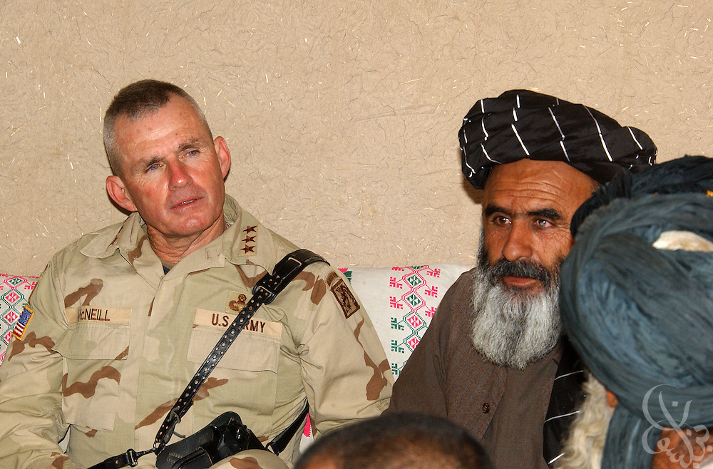 U.S. Army General Dan McNeill (L), Coalition Joint Task Force 180 commander, speaks with Governor of the Oruzgan province, Jan Mohammed Khan (C), and village elders  during a July 7, 2002 visit to Deh Rawud in Southern Afghanistan. McNeill used the visit to speak with Khan and the elders about the possibility of stationing more U.S. troops in the region, following an incident last week in which U.S. aircraft mistakenly targeted Afghan civilians celebrating in Deh Rawud.