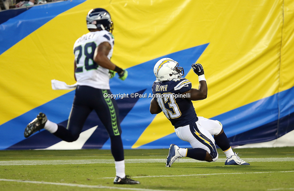 Seattle Seahawks defensive back Marcus Burley (28) looks on as San Diego Chargers running back Branden Oliver (43) celebrates after catching a 70 yard pass good for a third quarter touchdown that cuts the Seattle Seahawks lead to 13-12 during the 2015 NFL preseason football game against the Seattle Seahawks on Saturday, Aug. 29, 2015 in San Diego. The Seahawks won the game 16-15. (©Paul Anthony Spinelli)
