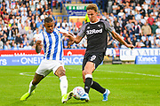 Kieran Dowell of Derby County (8) and Juninho Bacuna of Huddersfield Town (7) go for the loose ball during the EFL Sky Bet Championship match between Huddersfield Town and Derby County at the John Smiths Stadium, Huddersfield, England on 5 August 2019.