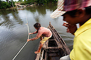 Pulling the passenger boat loaded with motorbikes and pasengers to get to the remote village of Prek Svey where the 10 Siamese crocodile hatchlings are being kept for protection..The 21st century was a good year for the Siamese Crocodile. In 2000 after being declared extinct in the wild they were 're-discovered' in the remote Cardamon Region of Cambodia. Then in June 2010 a nest of eggs was found by a team run by Fauna and Floras International (FFI), a British NGO, one of the world's oldest. 15 eggs were taken to safety and 10 successfully hatched in a 'fake' nest guarded by FFI staff. .Since that 2000 discovery much work has been done to find and research this critically endangered reptile. It is now believed that around 250 Siamese Crocodile are alive in the wild, the majority of which are in the Cardamon Mountains, down from tens of thousands before man started hunting them and encroaching on their habitat. .After successfully doing DNA tests to find 'pure blood' Siamese Crocs rather than those who have been cross-bred they plan to work with a breeding centre that will lead to the crocodiles being released back in to the wild.