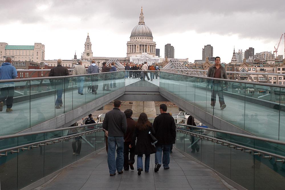 Un grupo de personas caminan por el Millenium Bridge mientras al fondo se ve la Catedral de San Pablo. Londres, 27-11-2005. (ivan gonzalez)