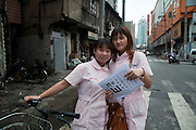 Two nurses pose for a portrait as in an old Shanghai neighborhood.
