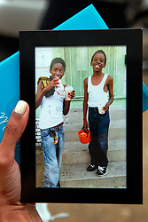 14 May 2014. New Orleans, Lousiana. <br /> A mourner holds up images from happier times/ L/R Lamichael and Miqual Jaclkson. <br /> at the funeral of 14 year old Miqual Jackson at the New Hope Baptist Church. Miqual Jackson was shot in the back of the head May 5th and died shortly afterwards. Surviving brother Lamichael was shot in the leg. 52 year old Gregory Johnson is wanted on 1st degree murder charges. Randy Pittman, 49, an associate of Johnson's was arrested on 3 counts of being a principal to 1st degree murder. The New Hope Baptist Church witnessed the funeral of 1 year old Londyn Samuels who was also gunned down in cold blood on the streets of New Orleans 8 months ago.<br /> Images courtesy Jackson family.<br /> Charlie Varley/varleypix.com