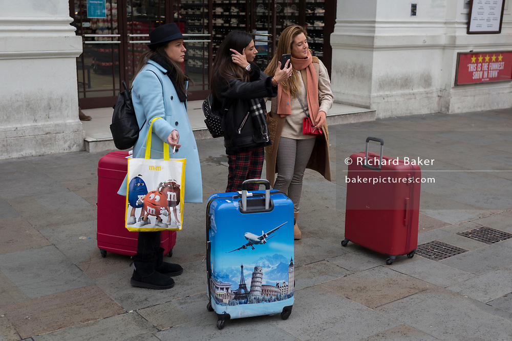 Three young women tourists pause with their suitcases and admire Piccadilly Circus on 12th November 2019, in London, England.