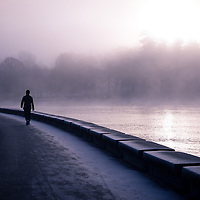 A long silhouetted person walking along a seawall covered in frost and fog.