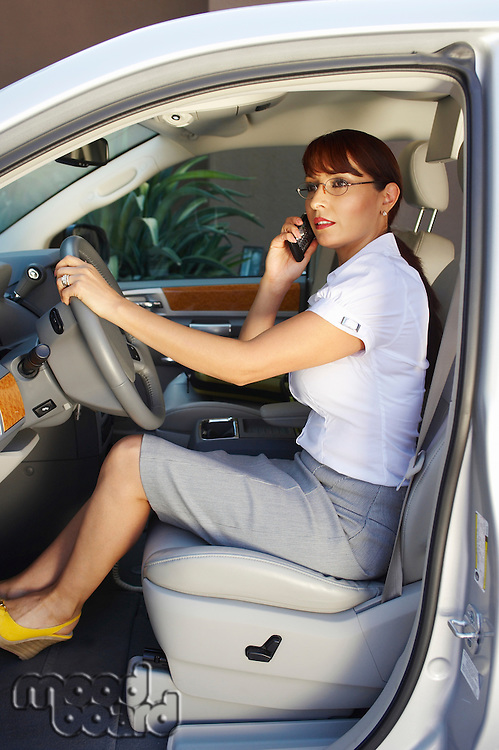 Business woman using mobile phone in car
