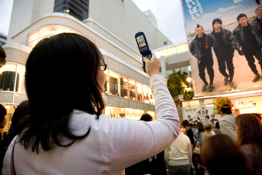 teenager girl making a photo of her favorite band in the Shibuya district of Tokyo Japan