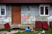 A girl is washing hairs in front of her parents house at the Roma settlement in Ostrovany.