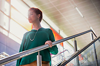 Portrait of young attractive businesswoman walking down stairs