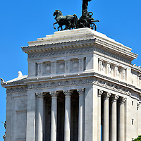 Quadriga Atop Altare della Patria in Rome, Italy <br /> As you stand in the Piazza del Campidoglio surrounded by the Capitoline Museums it is easy to see this prominent white building with Corinthian columns. This is the western end of Altare della Patria.  On top is a bronze horse-drawn chariot. La Quadriga dell&rsquo;Unit&agrave; is one of two statues of Victoria, the Roman goddess of Victory. As you walk down a large staircase/ramp called Cordonata and leave the Capitoline Hill it is not hard to wind your way around Via del Teatro di Marcello for a full view of this impressive monument.