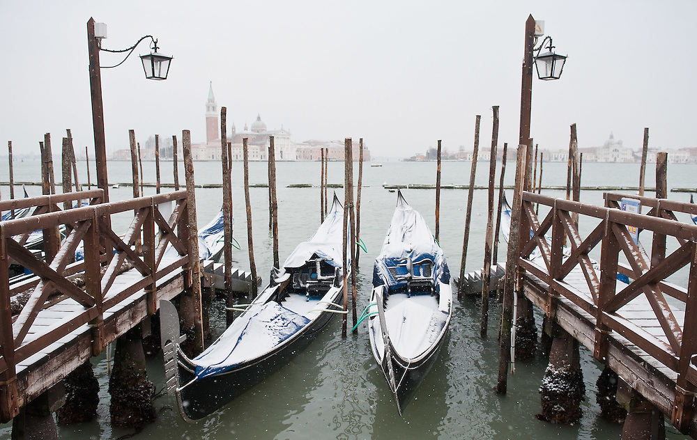 VENICE, ITALY - FEBRUARY 12:  Gondolas covered with snow are moored in St Mark's Basin on February 12, 2012 in Venice, Italy. Italy, like most of Europe, is experiencing freezing temperatures, with the Venice Lagoon freeezing for the first time in over 20 years.