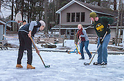 young adults playing ice hockey outside