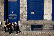 Reserved. Two men sit outside a blue-painted house in Lille, France, during the annual Braderie, or Lille Fair, which is one of the biggest gatherings in France, drawing up to 3 million people annually.