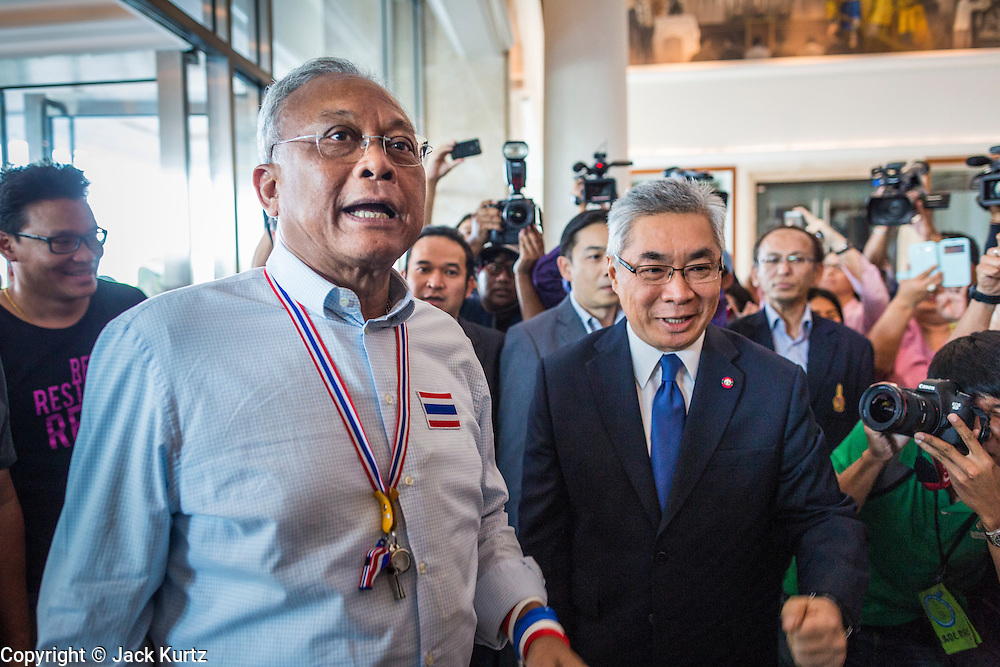 "08 APRIL 2014 - BANGKOK, THAILAND:  SUTHEP THAUGSUBAN (left) and KITTIPONG KITTAYARK, Permanent Secretary of the Thai Ministry of Justice, walk into the Ministry building in Bangkok. Several hundred anti-government protestors led by Suthep Thaugsuban went to the Ministry of Justice in Bangkok Tuesday. Suthep and the protestors met with representatives of the Ministry of Justice and expressed their belief that Thai politics need to be reformed and that corruption needed to be ""seriously tackled."" The protestors returned to their main protest site in Lumpini Park in central Bangkok after the meeting.   PHOTO BY JACK KURTZ"