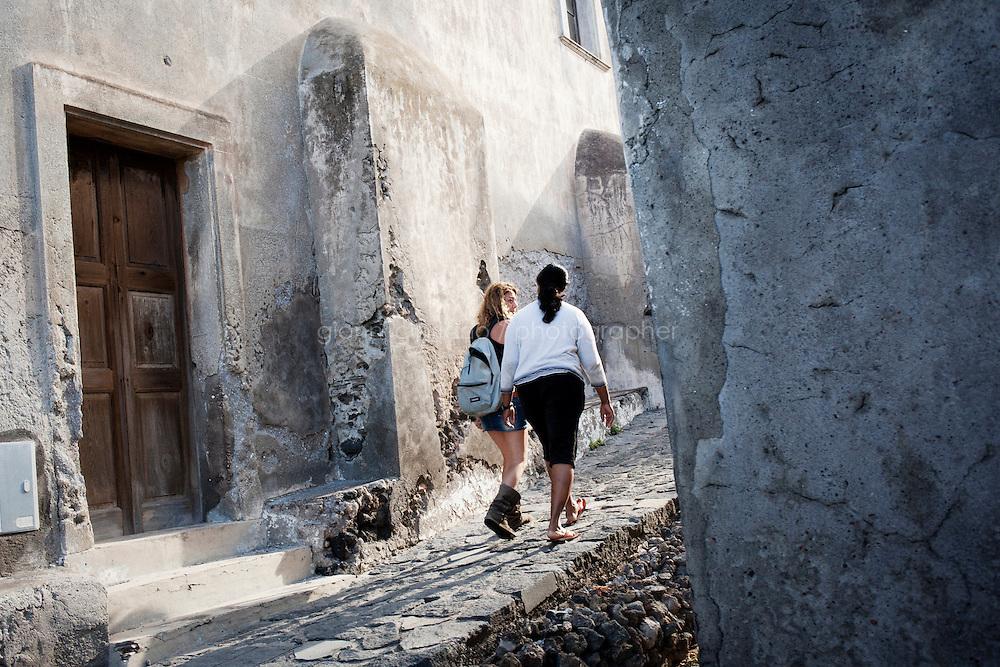 GINOSTRA (ME), ITALIA - 14 GIUGNO 2013: Due ragazze passeggiano tra le vie di Ginostra, sull'isola di Stromboli il 14 giugno 2013.<br /> <br /> Karol Hoffman, che vive da 30 anni insieme ad altri connazionali a Ginostra, considerato che il governo nazionale non ha mai provveduto a risolvere il problema di una centrale fotovoltaica malfunzionante, ha lanciato un appello alla Cancelliera Angela Merkel.