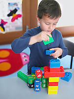 Boy playing with building blocks in classroom elevated view