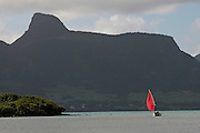 Pirogue with red sail returning to the island.