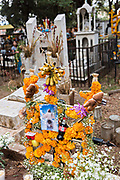 An elaborate floral decoration and food offerings on a gravesite during the Day of the Dead festival October 31, 2017 in Tzintzuntzan, Michoacan, Mexico. During the festival, which dates back hundreds of years to Aztec rituals, family members decorate the tombs of loved ones and celebrate them with gifts, food and altars.