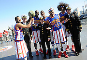 "The World Famous Harlem Globetrotters pose with Naval officers after playing an exhibition game on the flight deck of the Intrepid Sea, Air and Space Museum, Monday, Oct. 6, 2014, in New York.  The Globetrotters played the game to announce the dates for their 2014-15 North American Tour, during which they will honor a ""Hometown Hero,"" a current or past member of the U.S. armed forces, at each stop on their tour.  (Photo by Diane Bondareff/Invision for the Harlem Globetrotters/AP Images)"