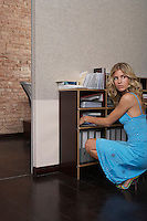 Woman squatting near bookcase in office