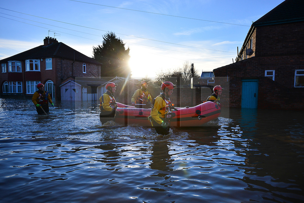 © Licensed to London News Pictures. 27/12/2015. York, UK.  Members of a Mountain Rescue team wade through flood waters on Huntingdon Road in York. Large areas of the North of England have been hit by severe flooding following unusually heavy rainfall in December. Photo credit: Ben Cawthra/LNP