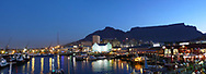 A panoramic night view of Cape Town harbor, the Victoria and Alfred Waterfront and Table Mountain, Cape Town, South Africa.