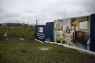 'Untitled, 2014' from the project 'The Fall and Rise of Ravenscraig' by photographer Colin McPherson.<br /> <br /> The photograph shows an advertising board for a housing development at the northern end of the Ravenscraig site, near Carfin.<br /> <br /> This project, photographed in 2014, looks at the topography of the post-industrial landscape at Ravenscraig, the site until its closure in 1992 of the largest hot strip steel mill in western Europe. In its current state, Ravenscraig is one of the largest derelict sites in Europe measuring over 1,125 acres (4.55 km2) in size, an area equivalent to 700 football pitches or twice the size of Monaco. It is currently being developed with a mix of housing, retail and the home of South Lanarkshire College and the Ravenscraig Regional Sports Facility.