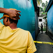 A body is seen lying in a callejon (alley) in the morning in Choloma, a small municipio (town) outside of San Pedro Sula, Honduras on February 10, 2017. The victim, Bryan Alexander Banegas, 18 year old contractor. The body was found at 6am, riddled with bullets. He went to work the day before and never came over.  The brother stands near the body as police continue their investigation.