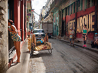 Two women watch as a woman talks to somebody through a window, on a street in Old Havana.