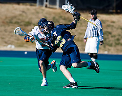 Navy midfielder Brendan Connors (23) protects the ball from Virginia midfielder Chris Clements (32).  The Virginia Cavaliers scrimmaged the Navy Midshipmen in lacrosse at the University Hall Turf Field  in Charlottesville, VA on February 2, 2008.