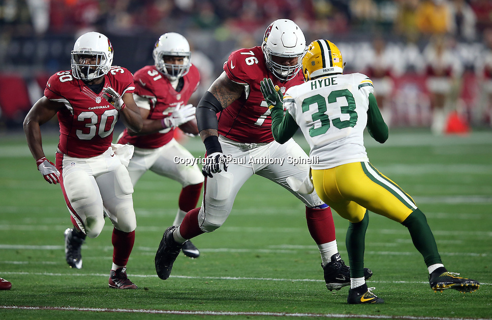 Arizona Cardinals guard Mike Iupati (76) and Arizona Cardinals running back Stepfan Taylor (30) lead block for Arizona Cardinals rookie running back David Johnson (31) while Green Bay Packers strong safety Micah Hyde (33) defends during the NFL NFC Divisional round playoff football game against the Green Bay Packers on Saturday, Jan. 16, 2016 in Glendale, Ariz. The Cardinals won the game in overtime 26-20. (©Paul Anthony Spinelli)